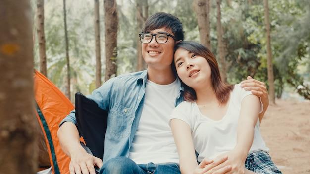 若いアジアのキャンピングカーのカップルは、森のテントのそばに椅子に座っています。キャンプ場で夏の日にリラックスして話している男性と女性の旅行者