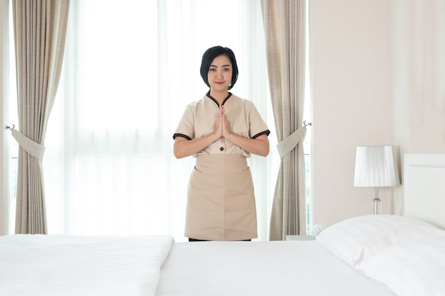 Горничная из молодой азии поднимает руку, чтобы выразить уважение в гостиничном номере