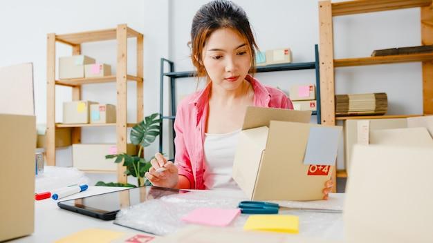 若いアジア起業家の実業家が在庫の製品購入注文を確認し、ホームオフィスでタブレットコンピューターに保存します。中小企業のオーナー、オンライン市場の配信、ライフスタイルのフリーランスのコンセプト。