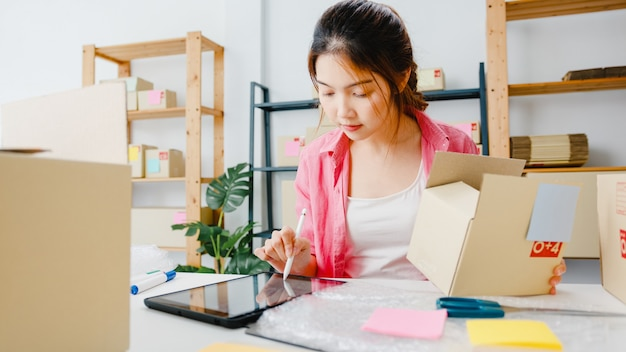 젊은 아시아 기업가 사업가 재고에 대한 제품 구매 주문을 확인하고 홈 오피스에서 태블릿 컴퓨터 작업에 저장합니다. 중소 기업 소유자, 온라인 시장 배달, 라이프 스타일 프리랜서 개념.