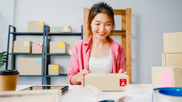 Young asia entrepreneur businesswoman packing product in cardboard box deliver to customer, working at home office. small business owner, start up online market delivery, lifestyle freelance concept.