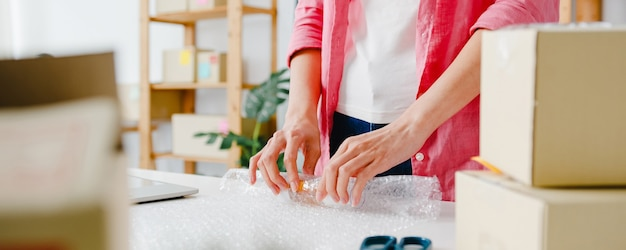 Предприниматель молодой азии предприниматель упаковки продукта в картонную коробку доставки клиенту, работая в домашнем офисе. владелец малого бизнеса, запуск онлайн-доставки на рынок, концепция внештатного стиля жизни.