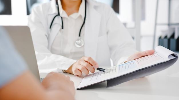 La giovane dottoressa asiatica in uniforme medica bianca che usa gli appunti sta offrendo grandi discorsi di notizie per discutere i risultati