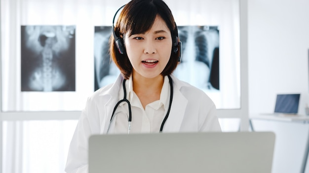 Young asia female doctor in white medical uniform with stethoscope using computer laptop talking video conference call with patient at desk in health clinic or hospital.