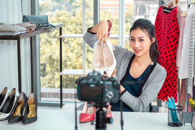 Young asia friendly girl live video blog and sales shoes in online e-commerce shopping