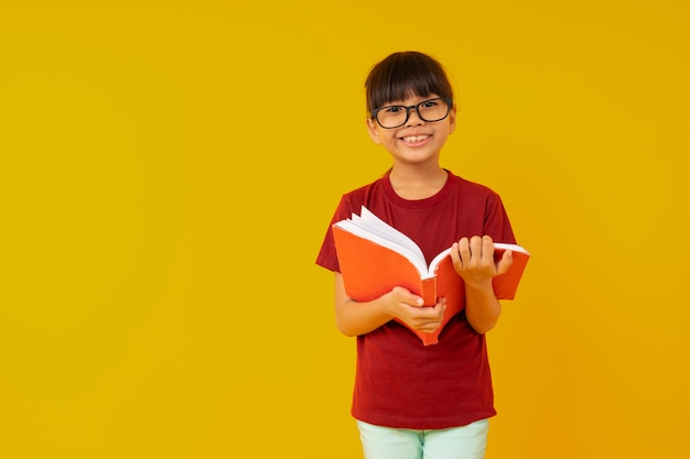 Young asia girl student with big smiled wearing glasses and red shirt open and read book