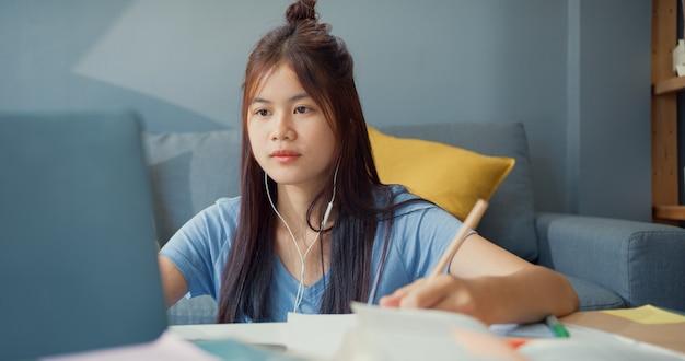 カジュアルウェアのヘッドフォンを使用している若いアジアの女の子のティーンエイジャーは、ラップトップコンピューターを使用して、自宅のリビングルームでオンラインで講義ノートを書く