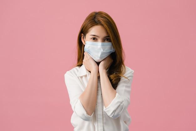 Молодая азиатская девушка в медицинской маске, уставшая от стресса и напряжения, уверенно смотрит в камеру, изолированную на розовом фоне.