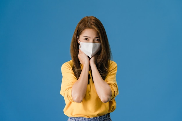 La giovane ragazza asiatica indossa una maschera medica, stanca di stress e tensione, guarda con sicurezza la telecamera isolata su sfondo blu. autoisolamento, allontanamento sociale, quarantena per la prevenzione del coronavirus.