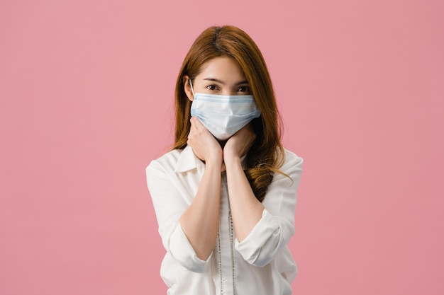 Young asia girl wear medical face mask, tired of stress and tension, looks confidently at camera isolated on pink background.