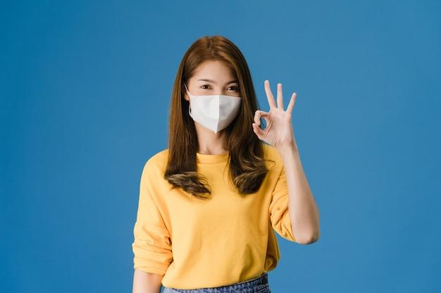 医療フェイスマスクジェスチャーokサインを身に着けている若いアジアの女の子はカジュアルな布に身を包んだし、青い背景に分離されたカメラを見てください。自己分離、社会的距離、コロナウイルスの隔離。