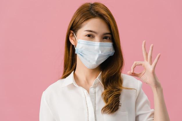 Молодая азиатская девушка в медицинской маске, жестикулирующая знаком с одетой в повседневную одежду и смотрящая на камеру, изолированную на розовом фоне.