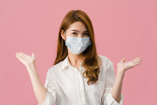 Young asia girl wearing medical face mask showing peace sign, encourage with dressed in casual cloth and looking at camera isolated on pink background. Free Photo