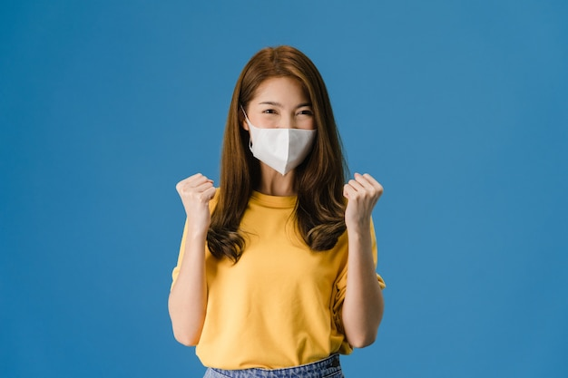 평화 기호를 보여주는 의료 얼굴 마스크를 착용하는 젊은 아시아 소녀, 캐주얼 옷을 입고 파란색 배경에 고립 된 카메라를보고 격려. 코로나 바이러스에 대한 사회적 거리두기, 격리.