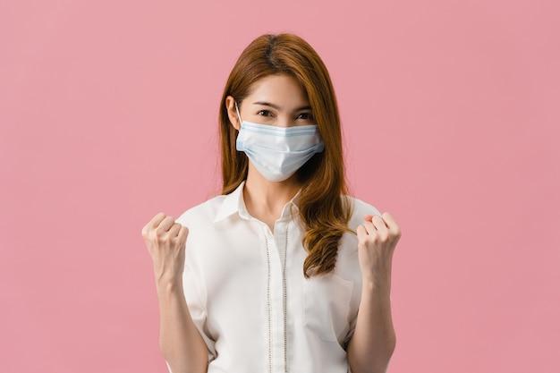Молодая азиатская девушка в медицинской маске показывает знак мира, поощряет одетой в повседневную одежду и смотрит в камеру, изолированную на розовом фоне.