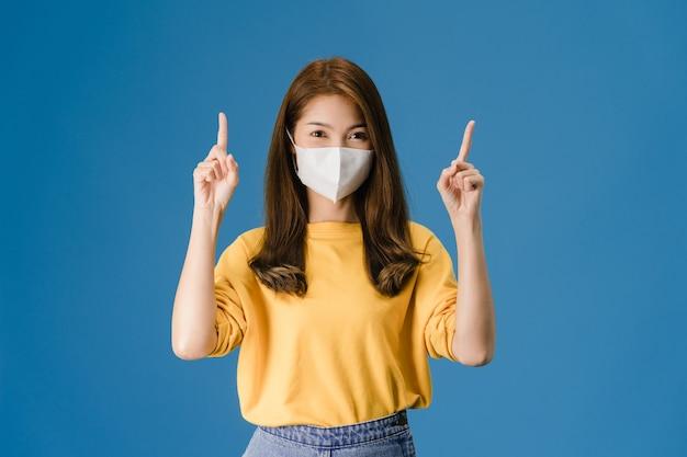 의료 얼굴 마스크를 착용하는 젊은 아시아 소녀 캐주얼 옷을 입고 파란색 배경에 고립 된 카메라를보고 빈 공간에서 뭔가 보여줍니다. 코로나 바이러스에 대한 사회적 거리두기, 격리.