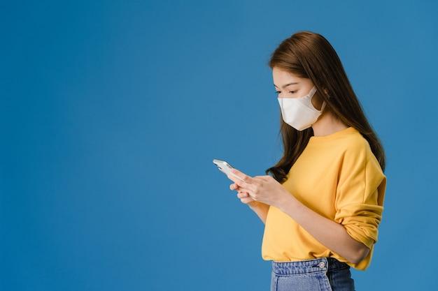 파란색 배경에 고립 된 캐주얼 의류를 입고 휴대 전화를 사용 하여 의료 얼굴 마스크를 착용하는 젊은 아시아 소녀. 코로나 바이러스 예방을위한자가 격리, 사회적 거리두기, 격리.