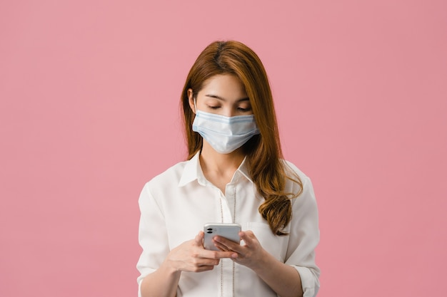 Молодая азиатская девушка в медицинской маске с помощью мобильного телефона, одетая в повседневную одежду, изолированную на розовом фоне.
