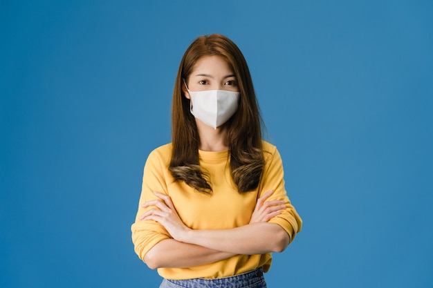 Young asia girl wearing medical face mask with arms crossed, dressed in casual cloth and looking at camera isolated on blue background. self-isolation, social distancing, quarantine for corona virus.