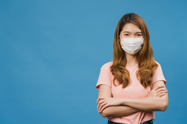Молодая азиатская девушка в медицинской маске со скрещенными руками, одетая в повседневную одежду и смотрит вперед, изолированную на синей стене