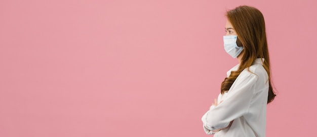 Young asia girl wearing medical face mask with dressed in casual cloth and look at blank space isolated on pink background.