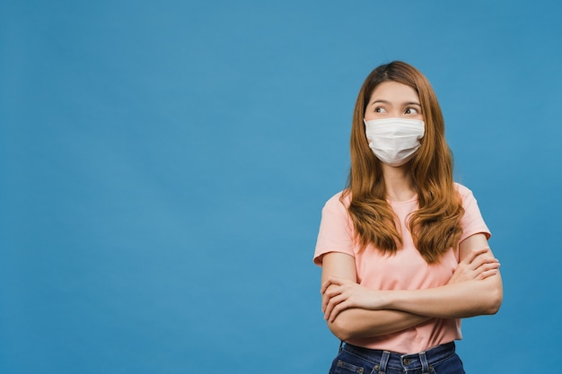 Young asia girl wearing medical face mask with dressed in casual cloth and looking at blank space isolated on blue background