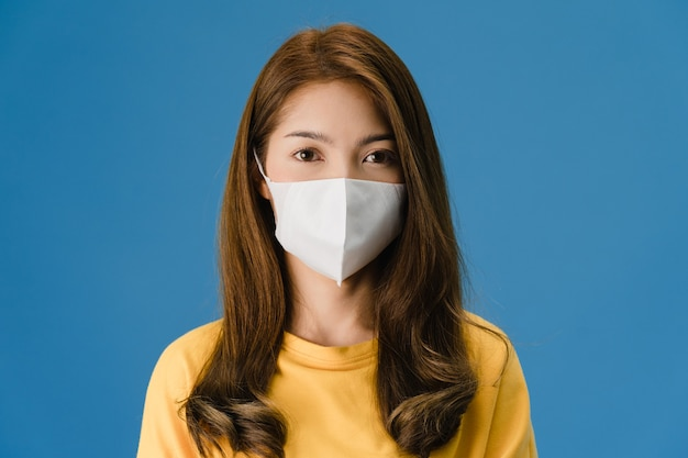 Young asia girl wearing medical face mask with dressed in casual clothing and looking at camera isolated on blue background. self-isolation, social distancing, quarantine for corona virus prevention.