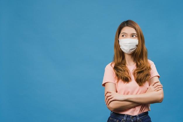 Молодая азиатская девушка в медицинской маске, одетая в повседневную одежду и смотрящая на пустое пространство, изолированное на синем фоне