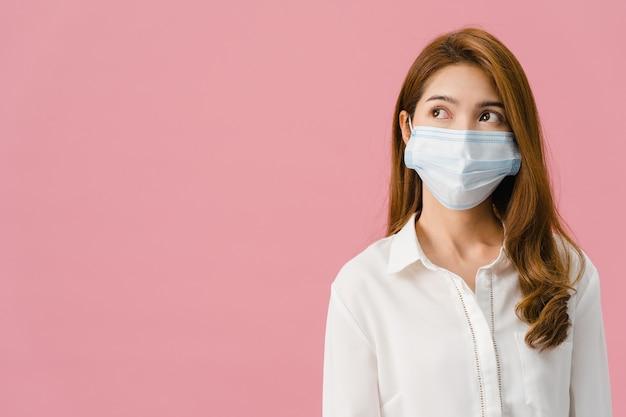 Молодая девушка азии в медицинской маске для лица с одетой в повседневную ткань и глядя на пустое пространство, изолированное на розовом фоне.