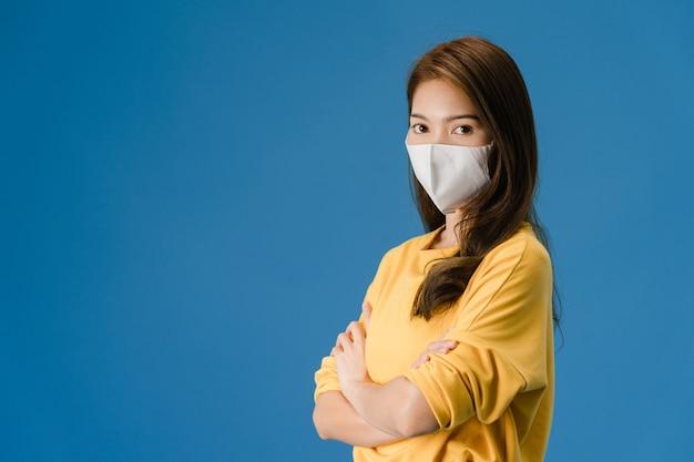 의료 얼굴 마스크를 착용하는 젊은 아시아 소녀 캐주얼 의류를 입고 파란색 배경에 고립 된 카메라를보고. 코로나 바이러스 예방을위한자가 격리, 사회적 거리두기, 격리.