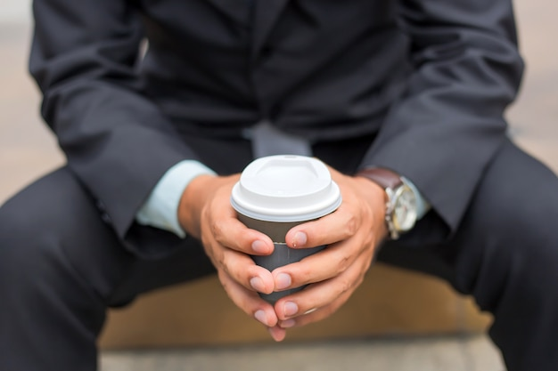 Young asia handsome businessman drinking hot coffee in the modern city.