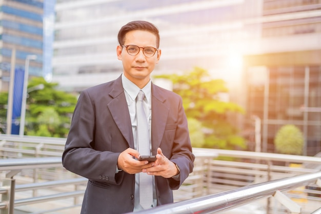 Young asia handsome businessman with his smartphone standing on walkway of modern city.