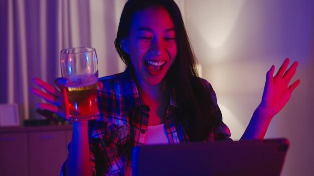 Giovane signora asiatica che beve birra divertendosi felice momento discoteca neon night party evento celebrazione online tramite videochiamata nel soggiorno di casa.