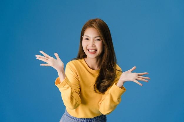 肯定的な表現で幸せを感じて、楽しくエキサイティングなカジュアルな布に身を包んだ、青い背景に分離されたカメラを見て若いアジア女性。幸せな愛らしい喜んで女性は成功を喜ぶ。