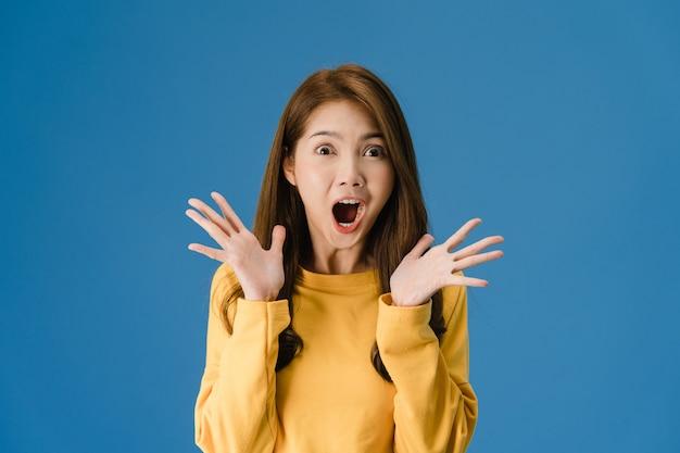 Giovane donna asiatica che sente felicità con l'espressione positiva, funky gioiosa sorpresa, vestita in un panno casual e guardando la telecamera isolata su sfondo blu. la donna felice adorabile felice si rallegra del successo