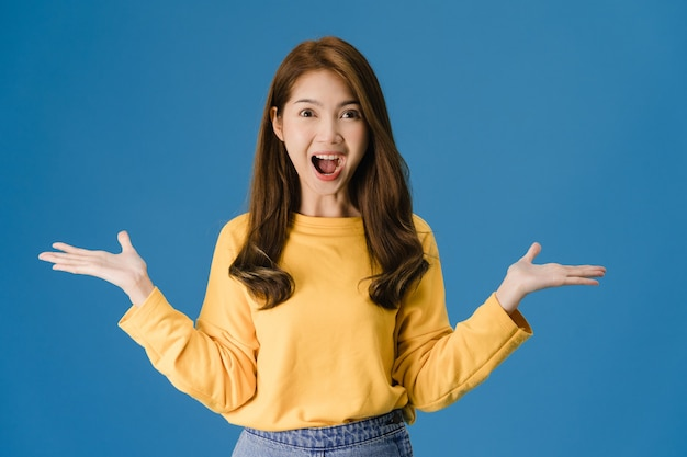 Young asia lady feeling happiness with positive expression, joyful surprise funky, dressed in casual cloth and looking at camera isolated on blue background. happy adorable glad woman rejoices success