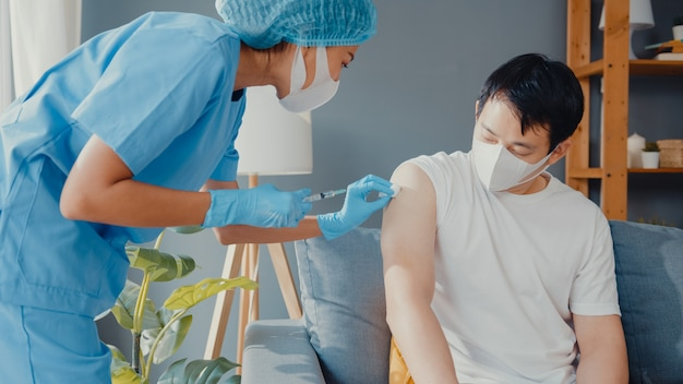 Young asia lady nurse giving covid-19 or flu antivirus vaccine shot to male patient wear face mask protection from virus