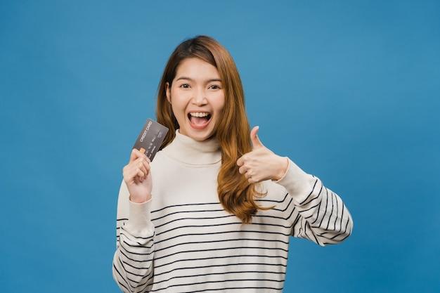 La giovane donna asiatica mostra la carta di credito con espressione positiva, sorride ampiamente, vestita con abiti casual sentendo felicità e stando isolata sulla parete blu
