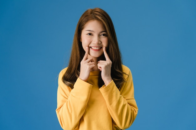 Young asia lady showing smile, positive expression, dressed in casual cloth and look at camera isolated on blue background. happy adorable glad woman rejoices success. facial expression concept.