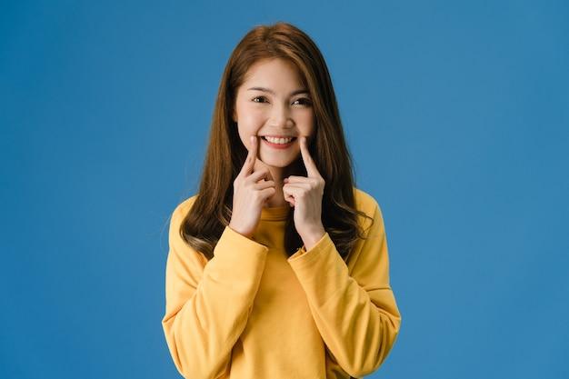 笑顔、肯定的な表現、カジュアルな布に身を包んだ若いアジア女性は青い背景に分離されたカメラを見てください。幸せな愛らしい喜んで女性は成功を喜ぶ。顔の表情のコンセプトです。