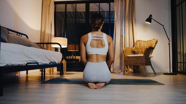 Young asia lady in sportswear doing yoga exercise working out in living room at home at night.