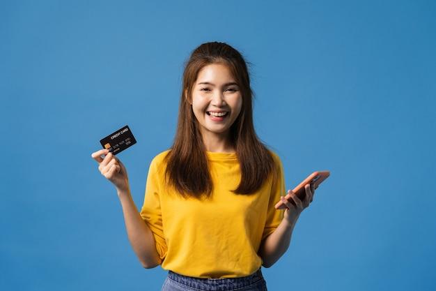 カジュアルな布に身を包んだ、青い背景に分離されたカメラを見て、肯定的な表現で携帯電話とクレジットバンクカードを使用して若いアジア女性。幸せな愛らしい喜んで女性は成功を喜ぶ。