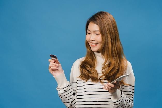 ポジティブな表情で電話とクレジットカードを使用している若いアジアの女性は、広く笑顔で、カジュアルな服を着て、青い壁に隔離されて立っています