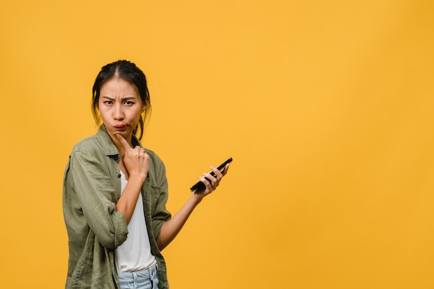 노란 벽에 평상복을 입은 긍정적인 표정으로 전화를 사용하는 젊은 아시아 여성