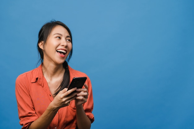 Young asia lady using phone with positive expression, smiles broadly, dressed in casual clothing feeling happiness and stand isolated on blue wall. happy adorable glad woman rejoices success.