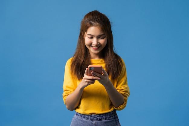 肯定的な表現で携帯電話を使用して若いアジア女性、広く笑顔、幸福感と立っている青い背景に分離されたカジュアルな服装に身を包んだ。幸せな愛らしい喜んで女性は成功を喜ぶ。