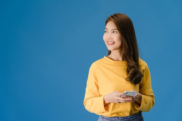 Молодая азиатская леди пользуется телефоном с позитивным выражением лица, широко улыбается, одетая в повседневную одежду, чувствуя счастье и стоя изолированной на синем фоне. счастливая очаровательная рада женщина радуется успеху.