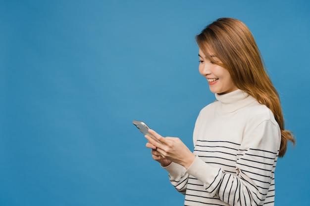 긍정적인 표정으로 전화를 사용하는 젊은 아시아 여성, 활짝 웃고, 캐주얼한 옷을 입고 행복을 느끼고 파란 벽에 고립되어 있습니다.
