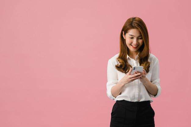 Молодая азиатская леди пользуется телефоном с позитивным выражением лица, широко улыбается, одетая в повседневную одежду, чувствуя счастье и стоя изолированной на розовом фоне.
