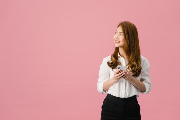 긍정적 인 표정으로 전화를 사용하는 젊은 아시아 아가씨는 행복을 느끼고 분홍색 배경에 고립 된 캐주얼 의류를 입고 광범위하게 미소 짓습니다.